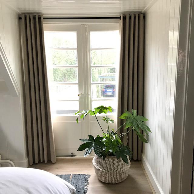 in de ouderslaapkamer matcht de stof mooi met het warme wit de gordijnen voor de openslaande deuren op de ouderslaapkamer hangen op een zwarte roede met